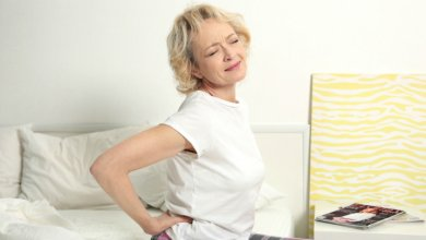 Elderly woman clutches lower back pain - Gillespie Approach–Craniosacral Fascial Therapy