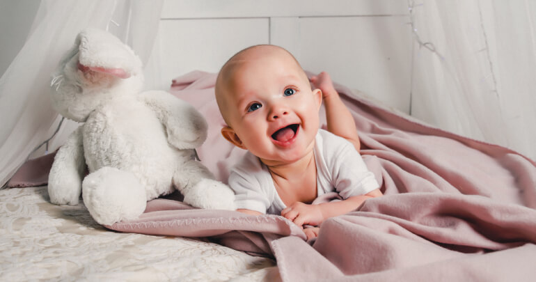 We treat tight people, not diseases - baby in bed with toy rabbit - Gillespie Approach–Craniosacral Fascial Therapy