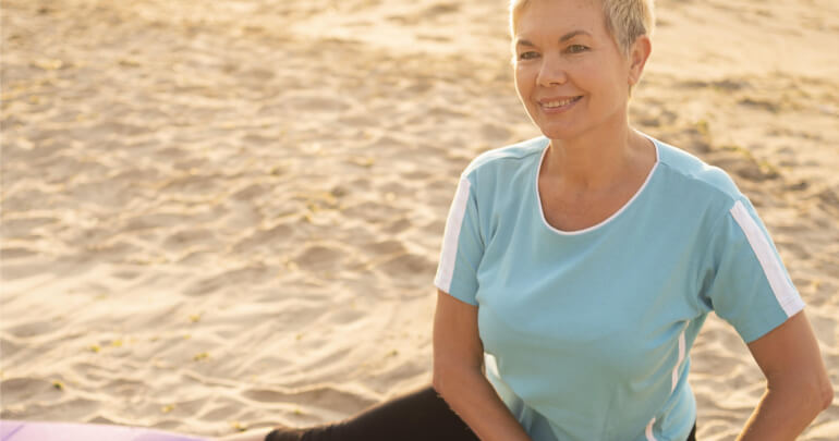 Aging and the fascial web - senior woman doing yoga on beach - Gillespie Approach–Craniosacral Fascial Therapy